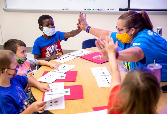 Kindergarten teacher Stacey Ericson gets high fives from Lamar and fellow kindergartners as they go through a vocabulary lesson during Camp Compass at Ridgely Elementary School in Springfield on Wednesday. The Camp Compass summer program was expanded to five sites across District 186 with 600 students in the program. [Justin L. Fowler/The State Journal-Register]