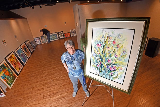 """Artist Helga Flower stands next to """"Enchantment,"""" a piece in acrylic that is one of 60 paintings on mixed media that was on display in Lake Superior State University's Arts Center Gallery."""