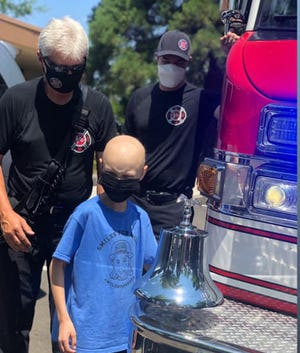 Miles Isbell  of Scott Valley rings a bell symbolizing his completion of chemotherapy treatments as firefighters from Medford., Ore., look on.