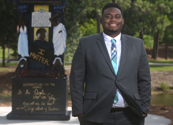 """Manny Lloyd, Cultural Enrichment Program Coordinator of the Upperman African American Cultural Center at UNCW, stands on campus with the new art piece, """"Because ItÕs Time"""", in the background in Wilmington, N.C., Friday, July 2, 2021. Lloyd is one of the StarNews 40 Under 40 honorees for 2021."""