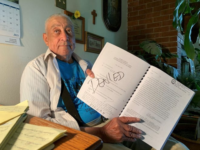 Bernard Bates holds a notebook of documents from the lawsuits he's been a part of while trying to get his farmland back.