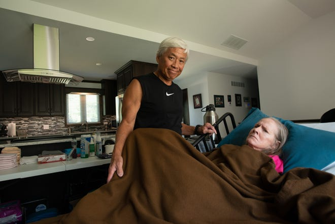 Nialson Lee takes care of his wife, Karen, inside their rebuilt house in west Topeka Friday afternoon. The couple's home burned down in 2018 from a suspected firework, and six months later, they were able to rebuild better than the original.