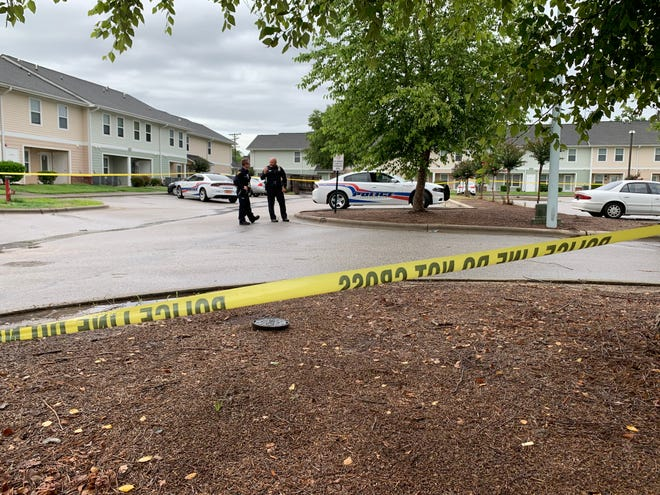 Fayetteville police officers stand in the parking lot of the Oak Run apartment Friday where was a man was found shot in a vehicle.