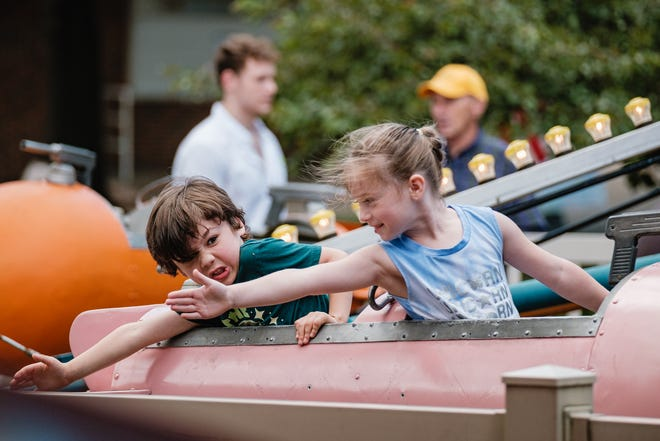Cousins Ezra Garcia (left), 4, and Mylee Finnicum, 6, enjoy a ride together Friday during the second day of First Town Days in New Philadelphia's Tuscora Park. The Garcia family was visiting from Maryland, but is originally from New Philadelphia. TIMES-REPORTER/ANDREW DOLPH