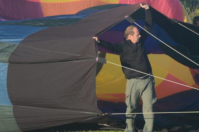 Larry Coan of New Hudson, MI, holds the envelope throat as he fills his hot air balloon with air before launch Friday.