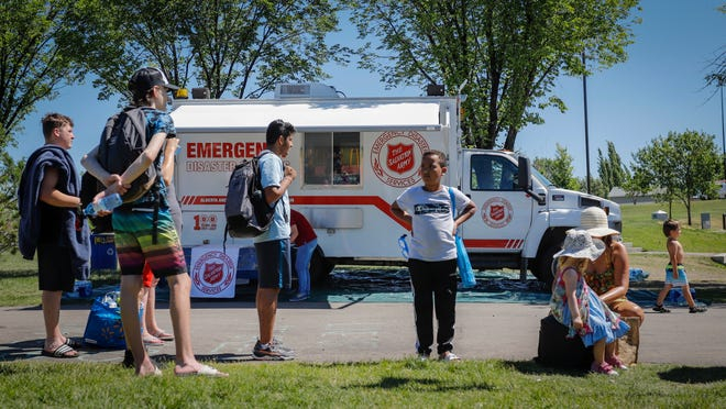 A Salvation Army EMS vehicle is setup as a cooling station as people lineup to get into a splash park while trying to beat the heat in Calgary, Alberta, on Wednesday.