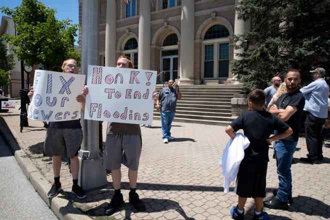Christopher Taylor, left, and his brother, Nicholas, who reside on Elm Street in Norwood, holds signs while protesting the City of Norwood for ignoring sewer issues for decades outside the Norwood Municipal Building in Norwood on Friday, July 2, 2021.