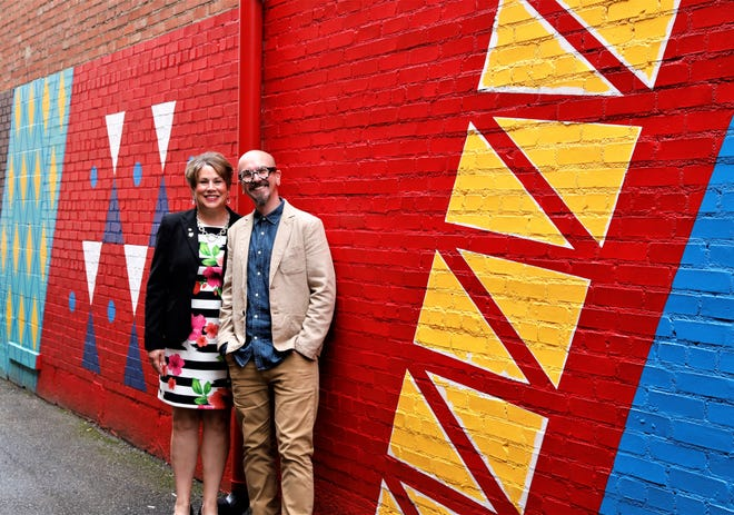 Christa Moody, left, and Jason Annecy stand in front of a mural dedicated to Fran Taylor and Gay Fad Studios in Center Alley on July 1. Taylor operated Gay Fad Studios from 1945 to 1963 in Lancaster, producing hand-painted glass.