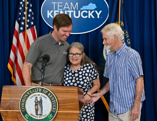 Gov. Andy Beshear, left, hugs Patricia Short, of Lexington, winner of the $1 million prize win in the Shot at a Million vaccine incentive drawing, July 2, 2021, in Frankfort. At right is her husband, Gary Short.