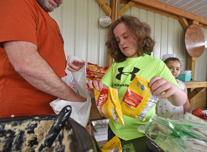 Avery Atwell, 10, bags up food for the hungry on Friday morning at the pavilion operated by People Helping People of North Central Ohio. Avery wanted to spend part of his birthday helping people and volunteering.