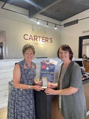 Beth Carter, left, presents Shena Loftis of Thornfield, Missouri, with her Facet Barcelona pendant as part of the Jews For You drawing at the 2021 Red White & Blue Festival.