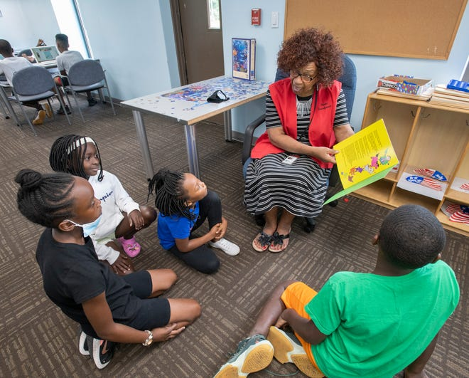 Foster grandparent Jacqueline Britt reads to Trinity Hull, 10, from left, Alondria Simmons, 8, Jayda McNeil, 8, and George Blount, 8, at the Brownsville Community Center in Pensacola on Thursday, July 1, 2021.