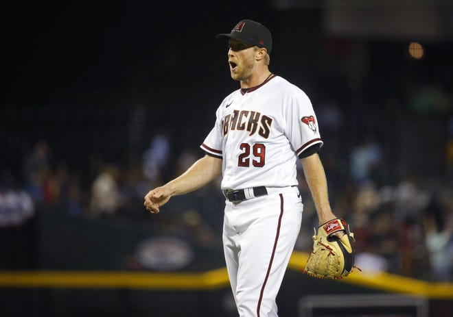 July 1, 2021; Phoenix, Arizona, USA; Diamondbacks' Merrill Kelly (29) reacts to allowing a two-run home run against the Giants during a game at Chase Field. Patrick Breen-Arizona Republic