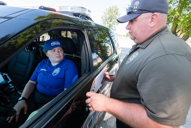 Michigan State Police Troooper Jerry Bockhausen, right, gives instructions to Port Huron Police Youth Academy student May Johnson, 17, during a simulated traffic stop Friday, July 2, 2021, at Port Huron High School.