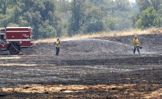 Firefighters hose down burned grass from the Twin Fire that burned several acres off Twin Creek Lane near Old Forty-four Drive between Redding and Palo Cedro on Friday, July 2, 2021.