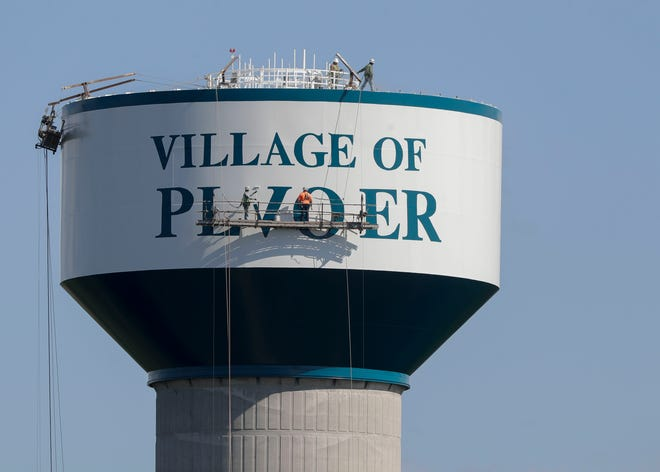 Paint crews work to fix a spelling error on Thursday, July 1, 2021, on the Plover water tower on Forest Avenue in Plover, Wis.