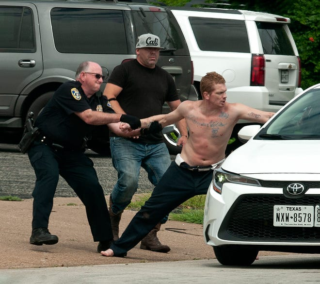 Police arrested a suspect after responding to a report of a man in traffic trying to fight motorists Friday morning.