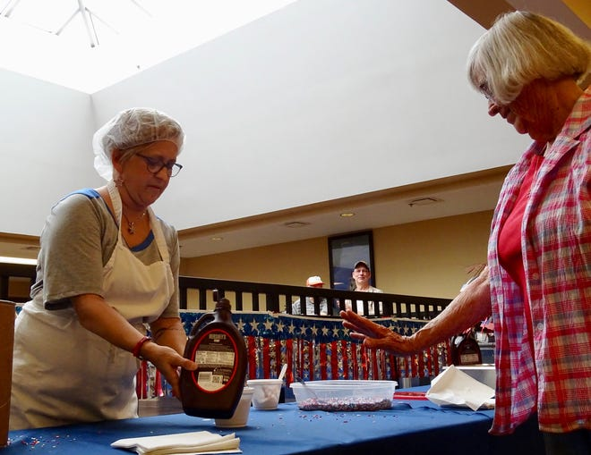 Sondra Karr, a regular at the Muskingum County Center for Seniors, customizes her dessert at an ice cream social on Thursday, July 1, 2021. It's the first event the senior center has hosted since the pandemic.