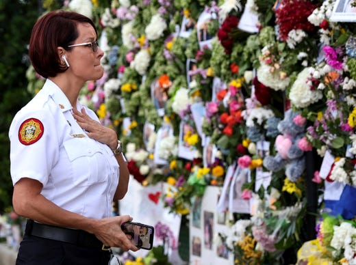 Miami-Dade Fire Rescue Chief Melanie C. Adams visit the makeshift memorial setup near the partially collapsed 12-story Champlain Towers South Condo in Surfside, Fla., Thursday, July 1, 2021.