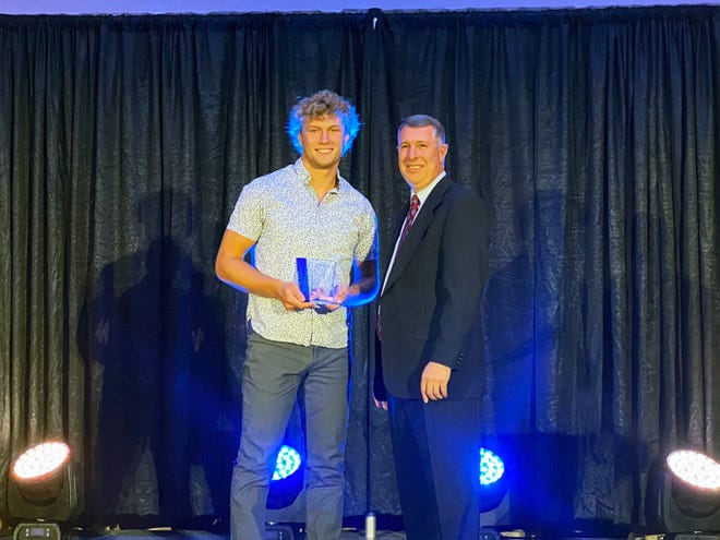 Andover High's Jack Johnson accepts the high school Male Athlete of the Year award from Mike Sharp, the Director of the Greater Wichita Area Sports Commission, at the Drury Hotel in Wichita, Kansas on Thursday, July 1.