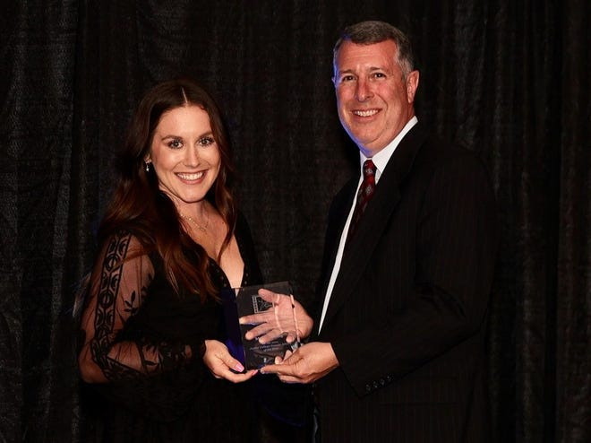 Madi Young accepts the Junior College Female of the Year award with Mike Sharp, Director of the Greater Wichita Area Sports Commission, at the Drury Hotel in Wichita, Kansas on Thursday, July 1.