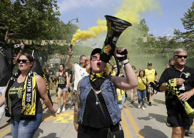 Suzi Clow, of the Columbus SoHud neighborhood, leads songs and chants Saturday while marching with fans down Nationwide Boulevard before the inaugural match at Lower.com Field between the Columbus Crew and the New England Revolution.