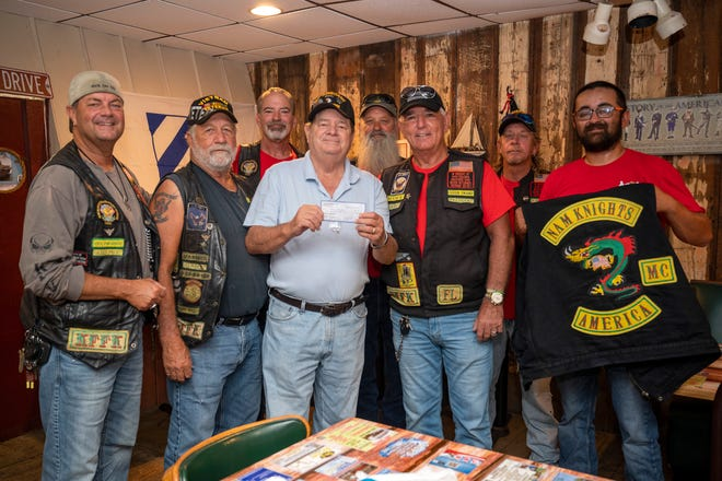 The NAM Knights Green Swamp chapter in Groveland presents Mike Whitaker a check for $500 to cover the cost of his home that insurance did not cover after his house caught fire. [Cindy Peterson/Correspondent]