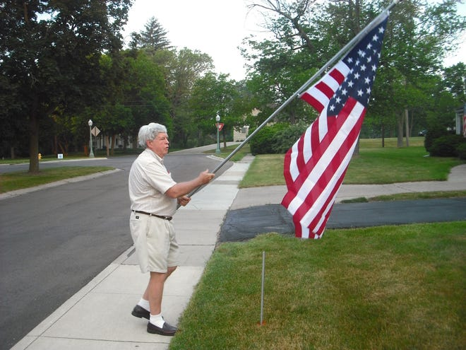 """The late David Siler, a 40-year member of the Kiwanis Club of Adrian and one of the founding members of the club's """"Avenue of Flags"""" project, places an American flag in the front lawn of an Adrian residence during the first year of the flag project in 2012. """"Avenue of Flags"""" has grown considerably year by year with major community support. The club currently places 1,450 flags around the community during six major patriotic holidays of the year."""