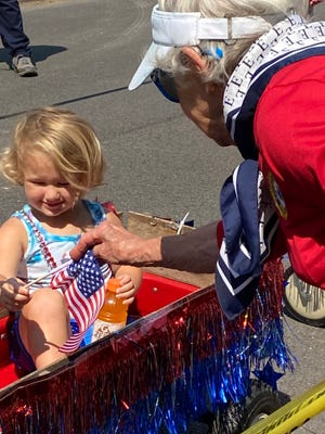 America was celebrated Saturday morning in Lincoln with an old fashioned walking parade. Great-grandmother Betty Gail Waggoner from Emden gives 2 year old Elizabeth Fitzpatrick of Lincoln a flag to wave during the parade line up. Over 30 people participated in the annual event that encourages all to enjoy a walk from Scully Park to the Lincoln Park District. Those walking were judged for prizes and winners were named before a long standing tradition of getting wet by running under the spray of a Lincoln Fire Truck.