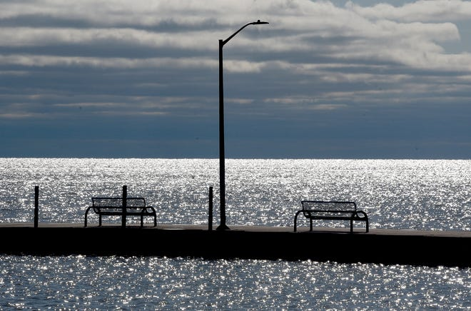 Lake Erie's glistening waters silhouette the benches on the Luna Pier pier in this Monroe News file photo. The harmful algal blooms that so often affect the lake are at the forefront of a new report issued by a coalition of local businesses.