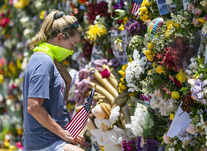 Miami Beach resident Tracey Lynne visits a makeshift memorial near the site of the collapsed Champlain Towers South Condo in Surfside, Fla., on Saturday, July 3, 2021. (Matias J. Ocner/Miami Herald via AP)