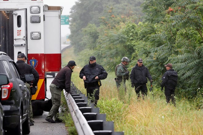 Police prepare to search a wooded area near the spot of a standoff with a group of armed men that partially shut down Route 95 on July 3 in Wakefield, Mass.