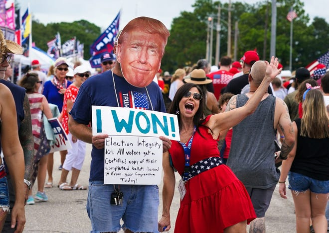 Wearing a cutout of Donald Trump's face, Marc DiMaggio of Punta Gorda has his photo taken with Lisa Rudolph during a rally for former President Donald Trump at the Sarasota Fairgrounds on July 3.