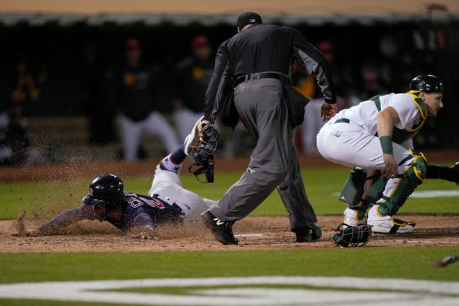 Boston Red Sox's Michael Chavis scores past Oakland Athletics catcher Sean Murphy, right, during the 10th inning  Friday in Oakland, Calif.