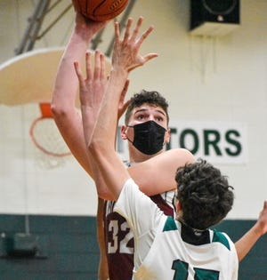 Bristol Central's Donovan Clingan attempts a shot over Northwest Catholic's Hayden Abdullah during a game last season. On Friday, Clingan committed to UConn.