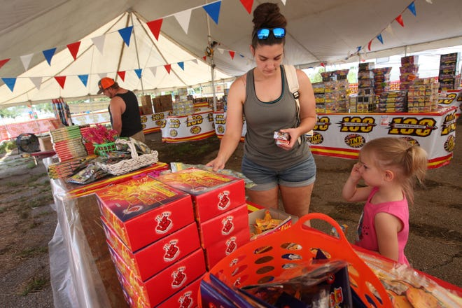 Mary Christian helps her 3-year-old daughter Emma shop for smaller fireworks Saturday morning at TNT Fireworks, corner of S.E. 45th Street and California Avenue, while her husband Brian looks at larger explosives.