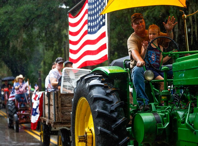 A man and child wave from atop a tractor during Micanopy's annual Independence Day parade on Saturday. [Chasity Maynard/Special to The Sun]