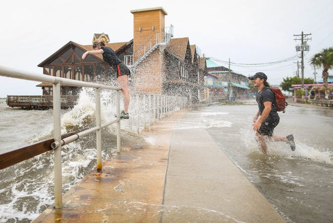 Holly McCoy, from left, and Filipe DeAndrade play in the rain and surf from Tropical Storm Colin along Dock Street in Cedar Key on Monday, June 6, 2016. Rob C. Witzel / Gainesville Sun