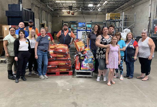Jackson, Tennessee's Walmart south associates, Jackson Animal Care Center Director Whitney Owen and the family of Matthew Hill stand in front of a pallet of pet food, Tuesday, June 29.
