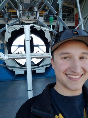 Bryson Stemock is shown here in front of the Apache Point Observatory 3.5mm telescope, which he uses frequently for his research. Stemock received the National Science Foundation Graduate Research Fellowship, which will provide three years of research funding to pursue his Ph.D.