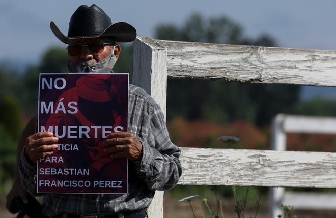 """Lauro Mendoza holds a sign that reads """"No more deaths""""  as community members gather to remember Sebastian Francisco Perez at Ernst Nursery and Farm in Saint Paul, Oregon, on Saturday, July 3, 2021."""
