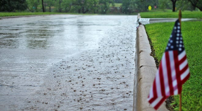Run off from early morning precipitation drains down Paseo de Vaca St. in the Santa Rita neighborhood near the site where the annual Fourth of July parade is held Saturday, July 3, 2021. The parade was cancelled due to the inclement weather.