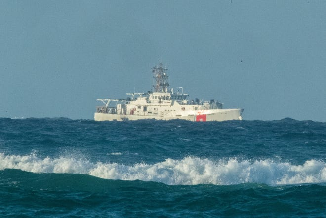 A U.S. Coast Guard cutter patrols the area of debris from a 737 cargo plane that crashed off Oahu on Friday.