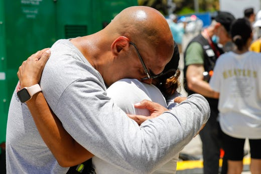 A member of the Miami-Dade Fire Rescue crew hugs a woman at the makeshift memorial near the site of the partially collapsed Champlain Towers South in Surfside, Florida on Saturday, July 3, 2021.