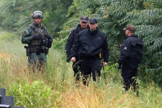 Police work on in the area of an hours long standoff with a group of armed men that partially shut down interstate 95, Saturday, July 3, 2021, in Wakefield, Mass.  Massachusetts state police say nine suspects have been taken into custody.