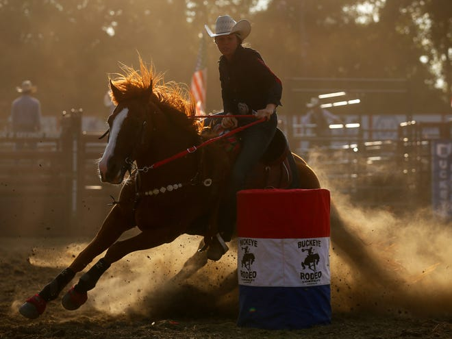 The sun sets as barrel racers put on a show for rodeo fans during the Buckeye Rodeo Company's stop at Barberton Speedway Saturday in Norton.