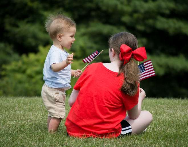 Ezra Tracy and Maddy Fisher wave their flags and enjoy the Independence Day celebration at Memorial Park in Barnesville.