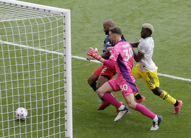 New England Revolution defender Andrew Farrell (2) scores an own goal while battling in front of the net with New England Revolution goalkeeper Matt Turner (30) and Columbus Crew forward Gyasi Zardes (11) during Saturday's 2-2 tie.
