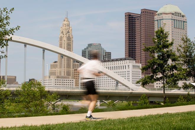 A runner jogs along the Scioto Mile greenway. It is one of many running trails for novices and those training for a marathon.