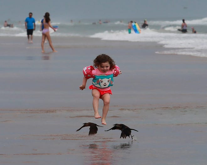 A little girl chases after birds on the beach in Daytona Beach Shores on Sunday, July 4th, 2021. Volusia County beach officials said Independence Day crowds this year were not as large as in previous years. Weather and an approaching tropical storm may have contributed to that. July 4, 2021.